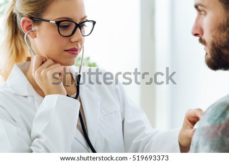 Portrait of female doctor checking patient heartbeat using stethoscope.