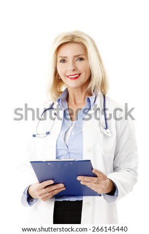 Portrait of female doctor holding clipboard in hands and checking patient list while standing against white background.  - stock photo