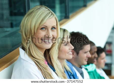 Portrait of female doctor smiling at the camera with her team in a line on stairs - stock photo