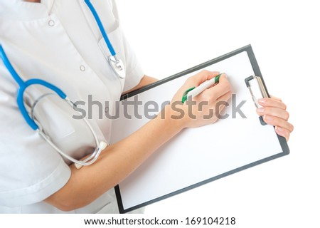 Portrait of female doctor with blue stethoscope on neck writing on blank clipboard on white background. Isolated woman doctor in white medical gown