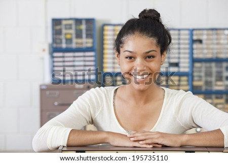 Portrait of female engineering student smiling at lab bench in electrical engineering laboratory
