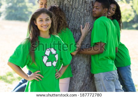 Portrait of female environmentalist at park with friends hugging tree in background - stock photo