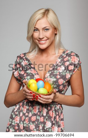 Portrait of female fashion model holding basket with Easter eggs
