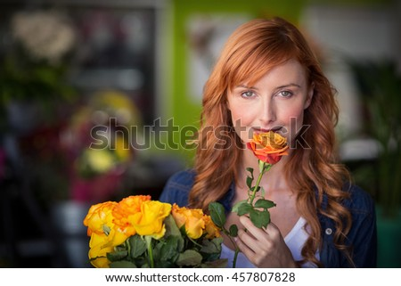 Portrait of female florist holding bunch of flowers in the flower shop - stock photo
