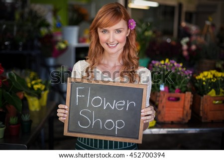 Portrait of female florist holding slate with flower shop sign in the flower shop - stock photo