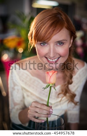 Portrait of female florist smelling a rose flower in the flower shop - stock photo