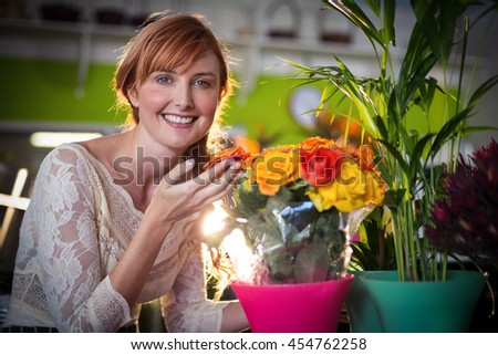 Portrait of female florist touching rose flowers in the flower shop - stock photo