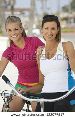 Portrait of female friends in sportswear standing together with bicycles