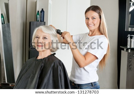 Portrait of female hairdresser ironing senior woman's hair in salon