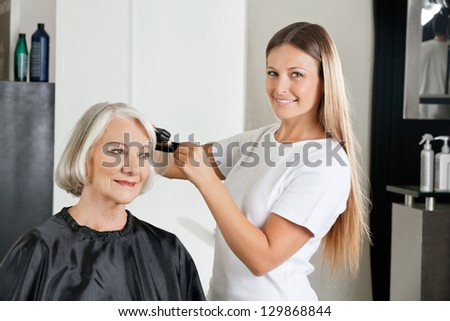 Portrait of female hairdresser with straightener ironing customer's hair at salon - stock photo