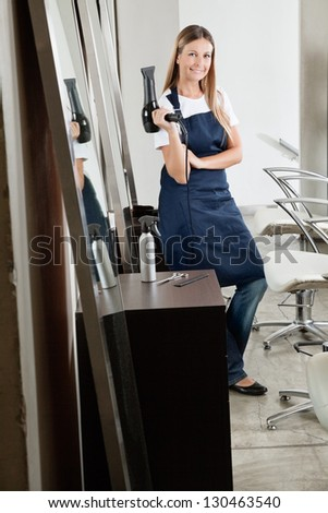 Portrait of female hairstylist with hair dryer in beauty salon - stock photo