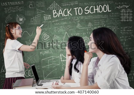 Portrait of female high school student explaining a lesson at her friends in the classroom