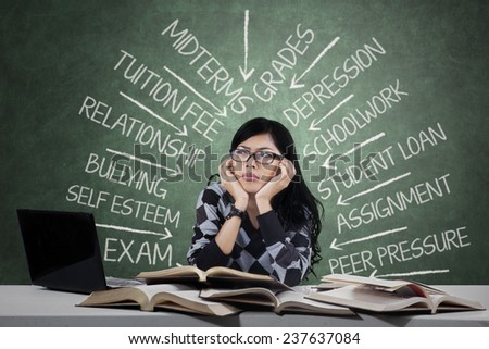 Portrait of female high school student thinking about her problems when studying - stock photo