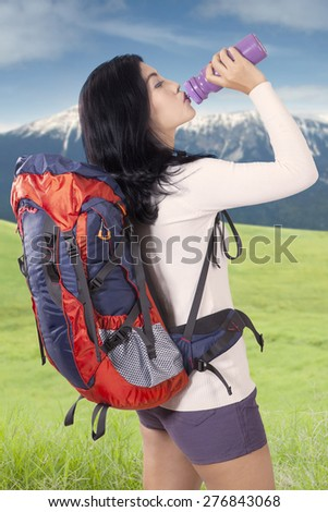 Portrait of female hiker carrying backpack and take a break while drinking fresh water from the bottle - stock photo