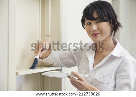 Portrait of female housekeeper cleaning shelf - stock photo