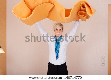 Portrait of female housekeeper with arms raised holding duvet in hotel room - stock photo