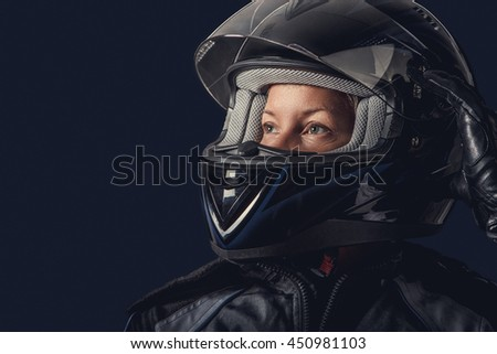 Portrait of female in motorcycle safety costume and black helmet.