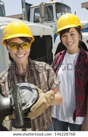 Portrait of female industrial worker buffing a truck engine cylinder with coworker standing besides her - stock photo