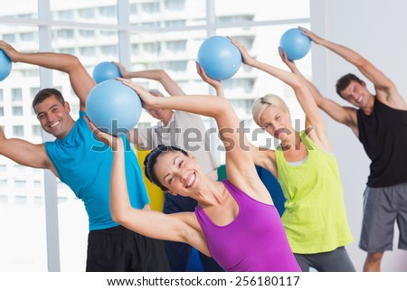Portrait of female instructor with class exercising with fitness balls in fitness club