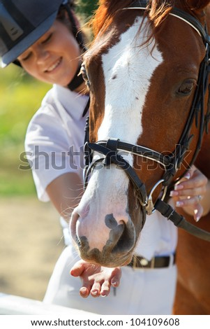 Portrait of  female jockey feeding purebred horse
