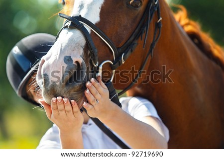 Portrait of  female jockey feeding purebred horse - stock photo