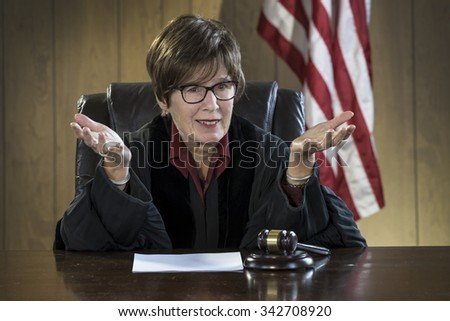 Portrait of female judge addressing the courtroom - stock photo