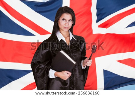 Portrait Of Female Judge With Book And Gavel Standing In Front Of Uk Flag - stock photo