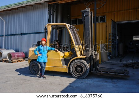 Portrait of Female Lift Truck Driver In Factory outdoor