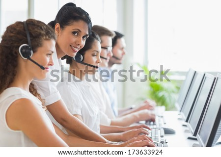 Portrait of female manager checking her staffs work in a call center - stock photo