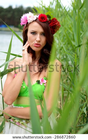 Portrait of female model with chestnut hairs, wearing wreath made of mixed flowers. Woman posing near lake surrounded by reeds.