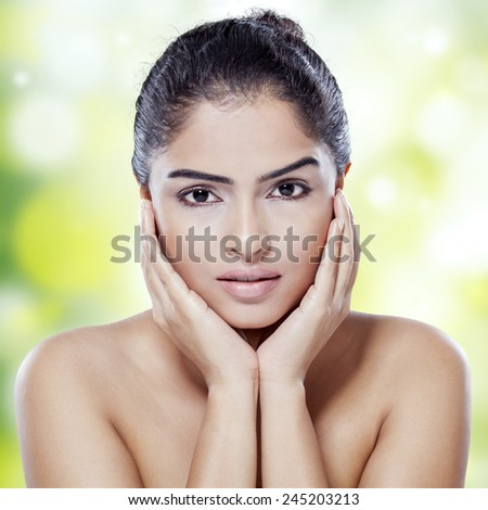 Portrait of female model with gorgeous face and perfect skin looking at camera against bokeh background