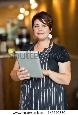 Portrait of female owner holding digital tablet while standing in cafeteria - stock photo