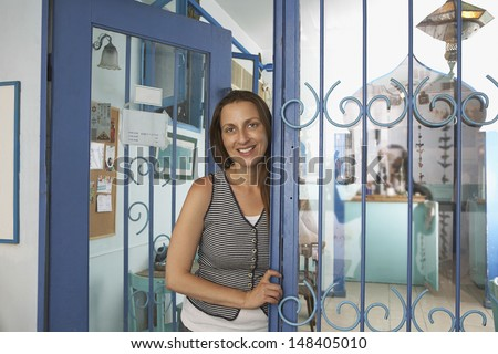 Portrait of female owner standing at the entrance of restaurant - stock photo