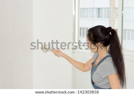 Portrait of female painting a wall with a roller as she decorates her home