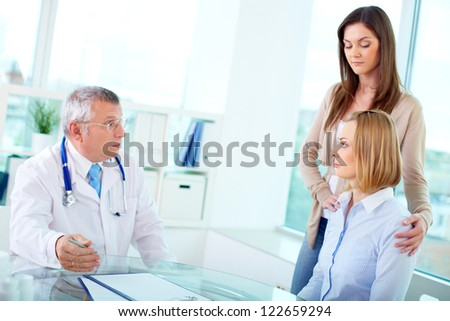 Portrait of female patients and mature doctor interacting at medical consultation in hospital - stock photo