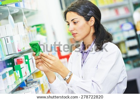 portrait of female pharmacist chemist woman in pharmacy drugstore - stock photo