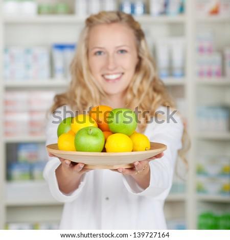 Portrait of female pharmacist holding plate of fruits in pharmacy - stock photo