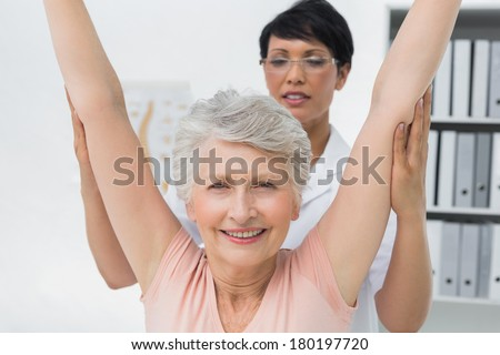 Portrait of female physiotherapist with senior woman raising hands in the medical office - stock photo
