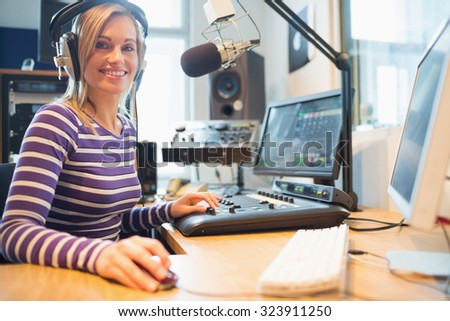 Portrait of female radio host using computer while broadcasting in studio - stock photo