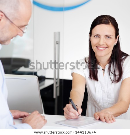 Portrait of female receptionist explaining form to patient in dentist clinic - stock photo