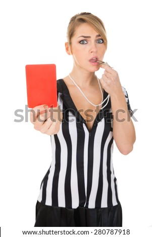 Portrait Of Female Referee Holding Red Card While Blowing Whistle - stock photo