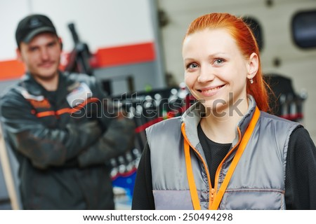 Portrait of female repairman auto mechanic in car auto repair or maintenance shop service station - stock photo