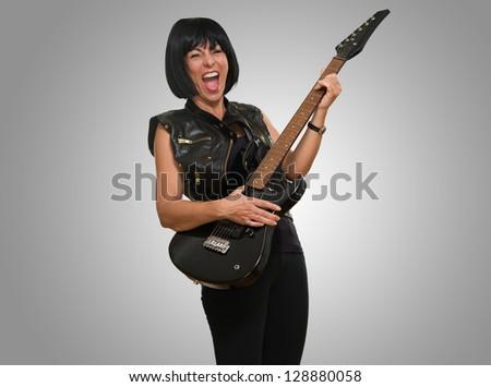 Portrait Of Female Rockstar against a grey background - stock photo