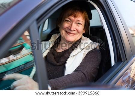Portrait of female senior driver smiling in car - stock photo