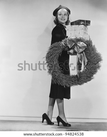 Portrait of female shopper with wreath and Christmas gifts - stock photo