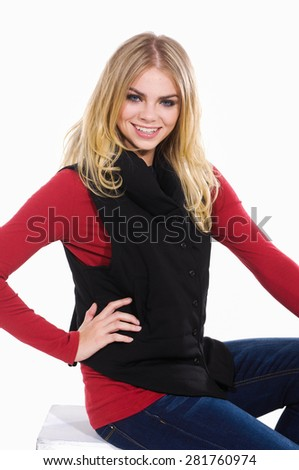 Portrait of female smile model in jeans sitting cube  - stock photo