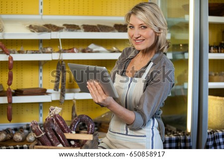 Portrait of female staff using digital tablet at counter in supermarket