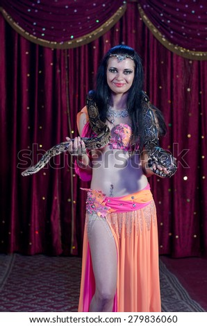 Portrait of Female Stage Performer, Snake Charmer Holding Python Snake Wrapped Around Shoulders Standing in front of Red Stage Curtain - stock photo
