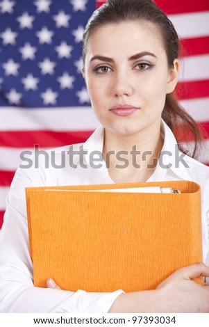 portrait of female student holding a folder over american flag - stock photo