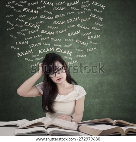 Portrait of female student studying with textbooks to prepare exam and looks dizzy